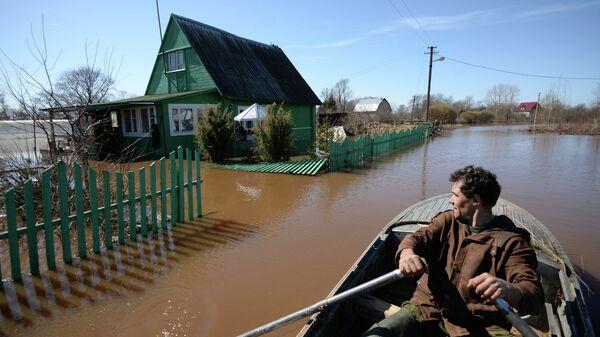 Мужчина плывет на лодке по подтопленной улице в деревне Русско в Новгородской области