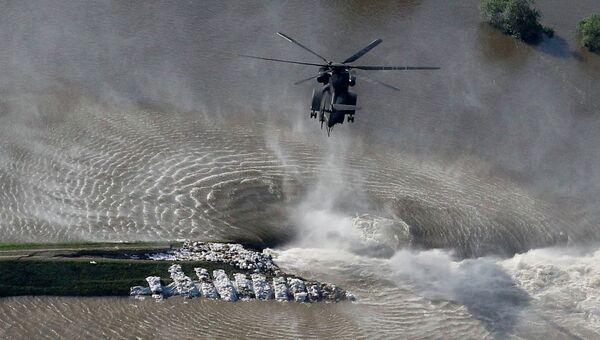Вертолет сбрасывает мешки с песком на месте разрушенной дамбы в Германии