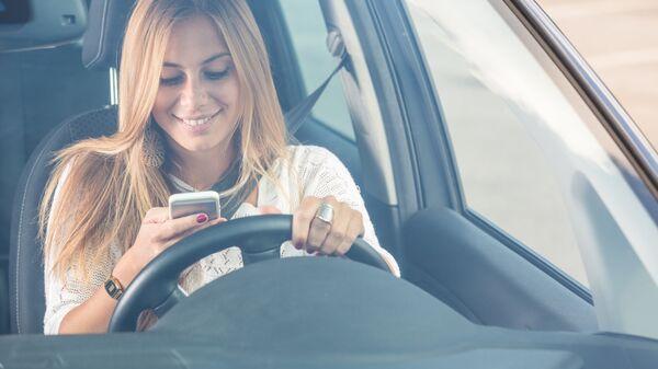 Девушка пользуется мобильным телефоном за рулем автомобиля. Архивное фото