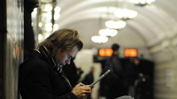Пассажир пользуется планшетным компьютером, архивное фото