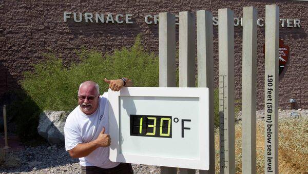 Сотрудник центра для туристов города Фёрнес-Крик возле термометра в Долине Смерти в Калифорнии. На термометре 54,4 градуса по Цельсию