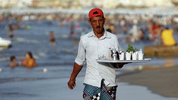 Мужчина продает кофе и чай на пляже в Александрии