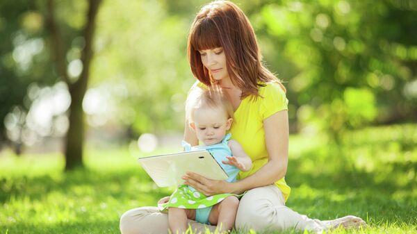 Женщина показывает ребенку видео на планшете. Архивное фото