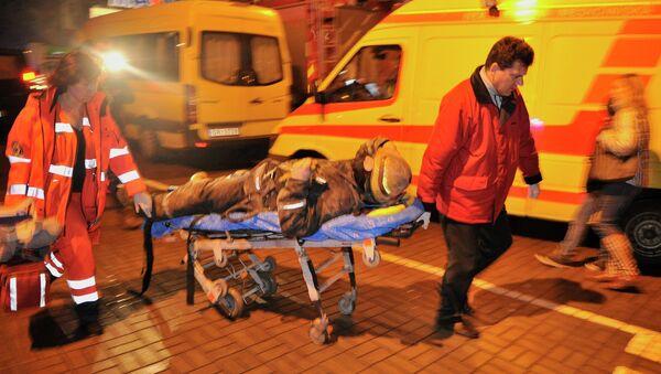 Медики скорой помощи везут носилки с сотрудником пожарно-спасательной службы, пострадавшим при разборе завалов от обрушения крыши в торговом центре Maxima
