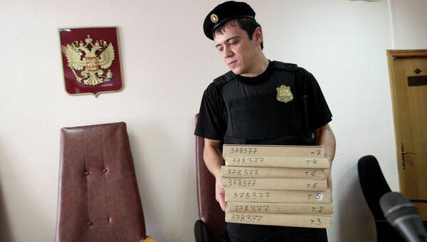 Судебный пристав держит в руках папки с документами, архивное фото
