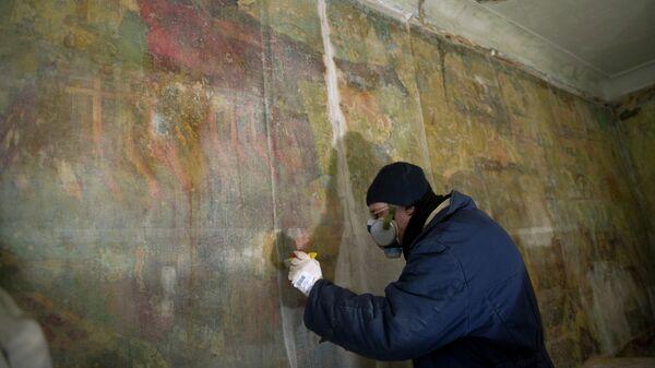 Реставратор за работой по восстановлению коммунистических фресок 30-х годов, обнаруженных в полуразрушенном доме Стройбюро ансамбля зданий Болшевской трудовой коммуны