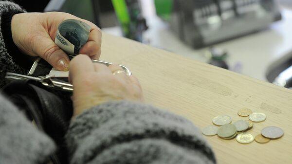 Женщина расплачивается в кассе
