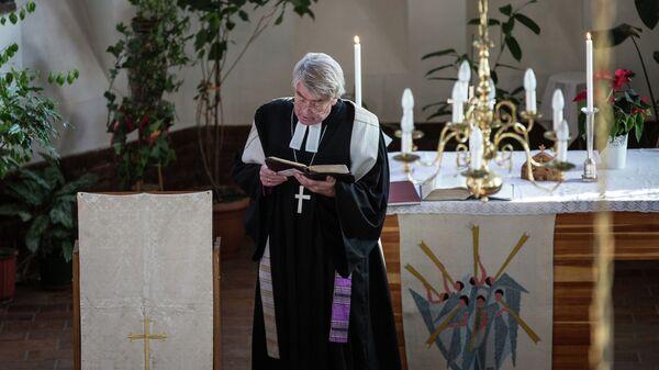Пастор общины Святого Павла во Владивостоке Манфред Брокманн проводит Рождественскую службу в лютеранской церкви