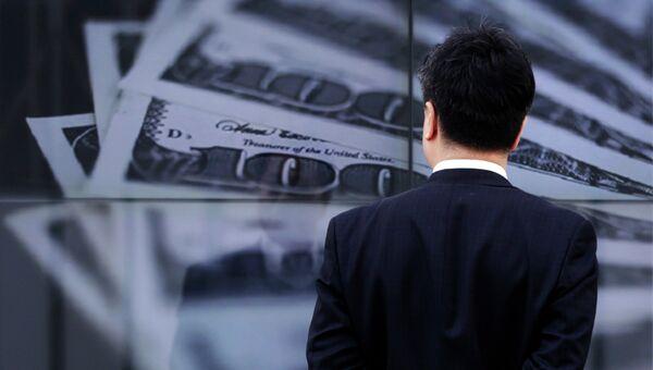 Бизнесмен смотрит на экран с изображением 100-долларовых банкнот, архивное фото