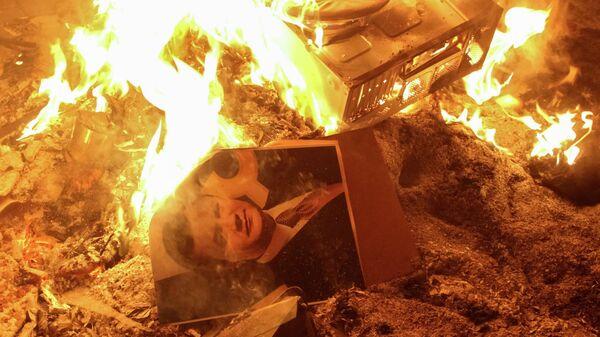 Портрет украинского президента Виктора Януковича горит возле разрушенного здания службы безопасности во Львове 19 февраля 2014.