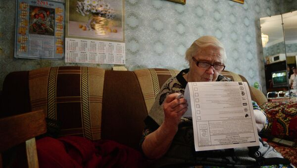 Женщина голосует на дому во время выборов, архивное фото