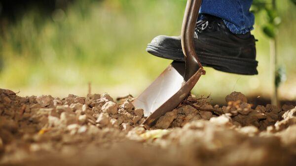 Мужчина копает землю