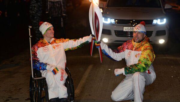 пауэрлифтер Владимир Кривуля (слева) во время эстафеты Олимпийского огня в Краснодаре.