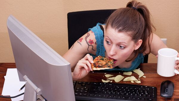 Девушка ест за компьютером. Архивное фото