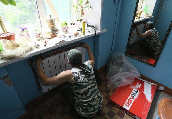 Рабочий устанавливает радиатор отопления