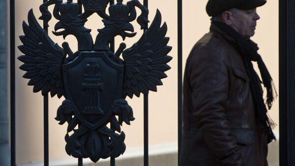 Мужчина идет мимо здания Генеральной прокуратуры России на улице Петровка в Москве. Архивное фото