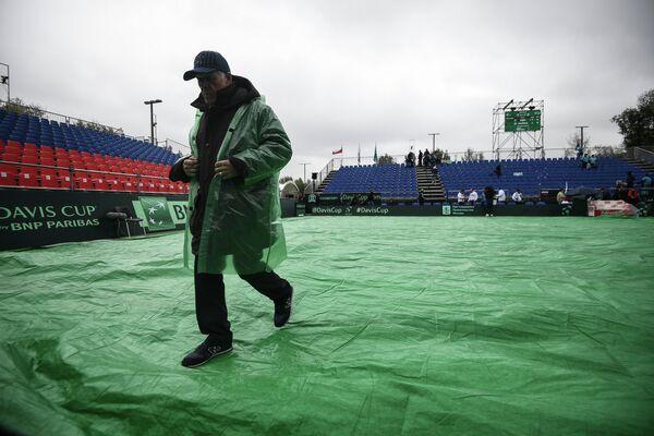 Сотрудник на корте Национального теннисного центра в Москве во время матча Кубка Дэвиса