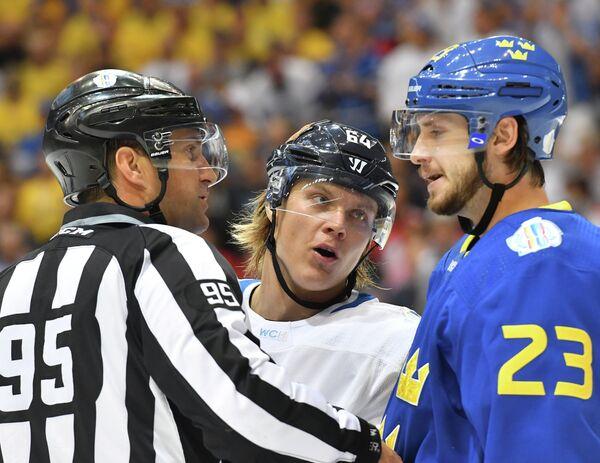 Форвард сборной Финляндии Микаэль Гранлунд ( центре) и защитник сборной Швеции Оливер Экман-Ларссон (справа)