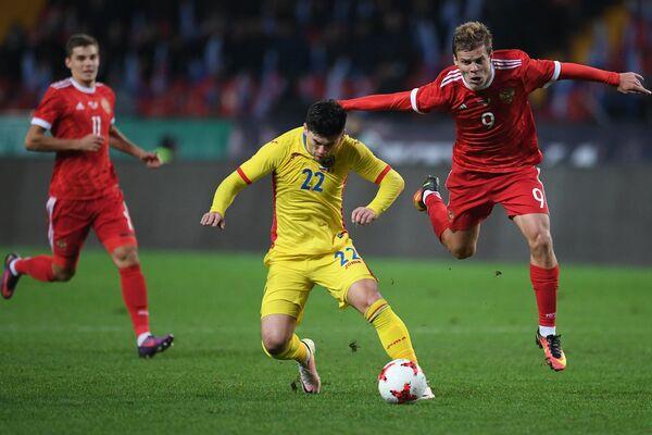 Защитник сборной Румынии Кристиан Сэпунару (слева на первом плане) и форвард сборной России Александр Кокорин