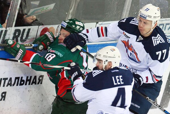 Нападающий Ак Барса Михаил Варнаков и хоккеисты Металлурга Крис Ли и Денис Казионов (слева направо)