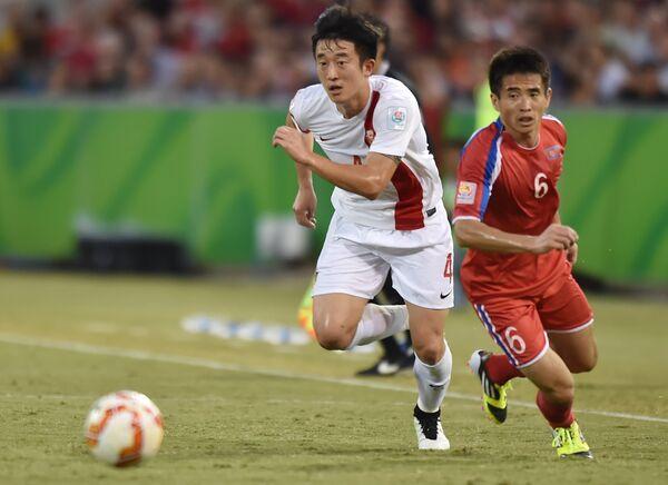 Футболист сборной Китая Цзян Чжипэн (слева)