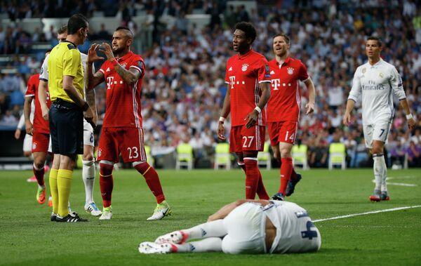 Полузащитник Баварии Артуро Видаль (второй слева) спорит с арбитром матча Реал - Бавария Виктором Кашшаи