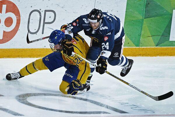 Форвард сборной Финляндии Яни Лаюнен (справа) и защитник сборной Швеции Расмус Далин
