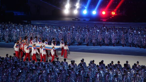 Спортсмены олимпийской сборной России выносят российский флаг
