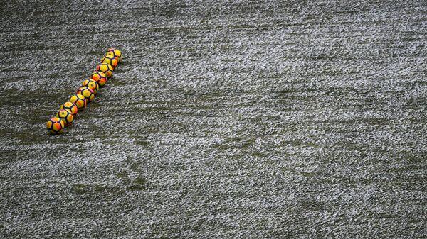 Желтые футбольные мячи на заснеженном поле