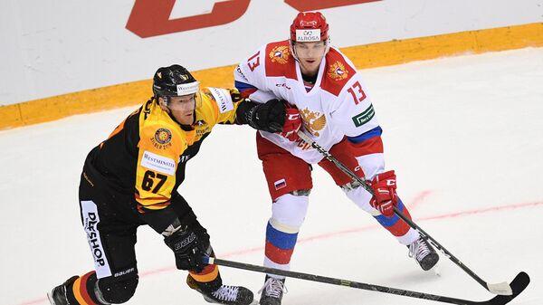 Защитник сборной Германии Бернхард Эбнер и защитник олимпийской сборной России Николай Демидов (справа)