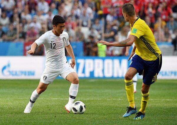 Защитник южно-корейской сборной Ким Мин Ву и защитник сборной Швеции Микаэль Люстиг (Слева направо)