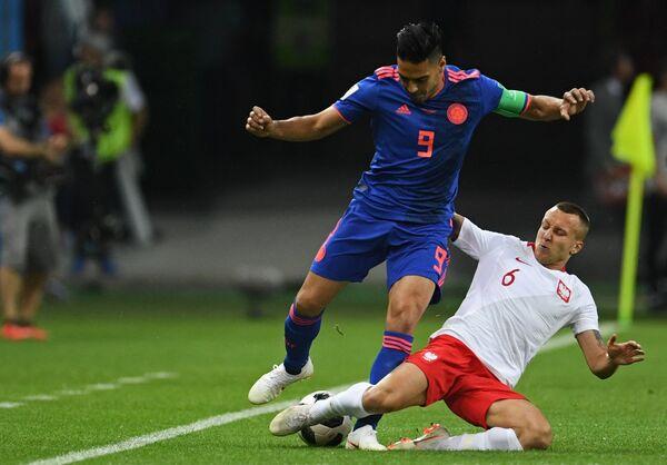 Нападающий колумбийской сборной Радамель Фалькао и польский полузащитник Яцек Гуральски (Слева направо)