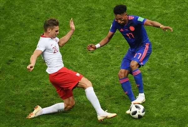 Польский защитник Лукаш Пищек и защитник сборной Колумбии Хоан Мохика (Слева направо)