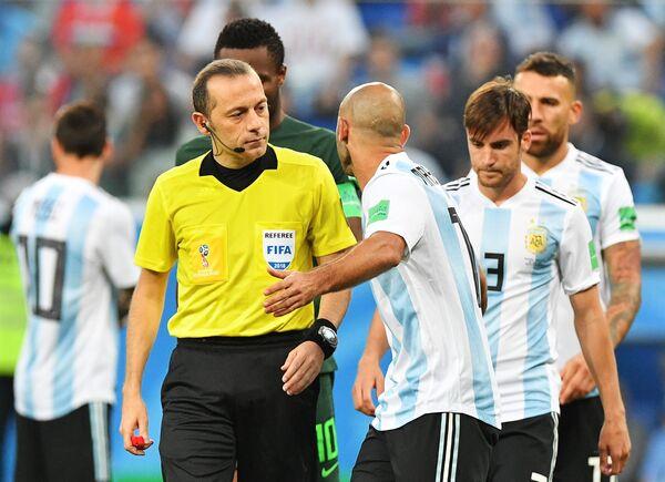 Главный судья Джюнейт Чакыр и аргентинский защитник Хавьер Маскерано (Слева направо)