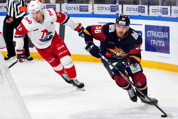 Игрок ХК Металлург Яков Рылов (справа) и игрок ХК Локомотив Артём Ильенко