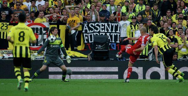 Вратарь Боруссии Роман Вайденфеллер отбивает удар полузащитника Баварии Арьена Роббена (второй справа)