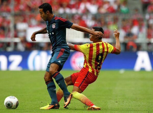 Игрок ФК Бавария Тьяго Алькантара (слева) и игрок ФК Барселона Алексис Санчес