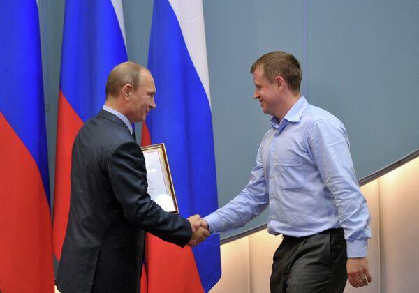 Президент России Владимир Путин (справа) вручает благодарственную грамоту мастеру спорта международного класса Максиму Соловьеву