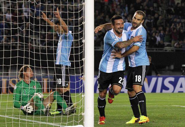Футболисты сборной Аргентины Серхио Агуэро и Родриго Паласио поздравляют с забитым мячом Эсекьеля Лавесси