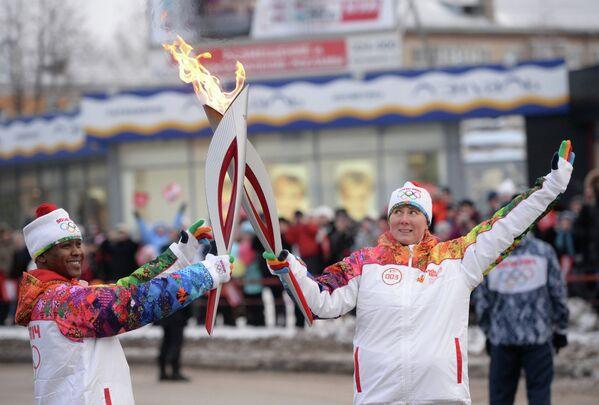 Факелоносец Юлия Антохина и хирург-онколог Мартин Халане во время эстафеты олимпийского огня в городе Каменск-Уральский