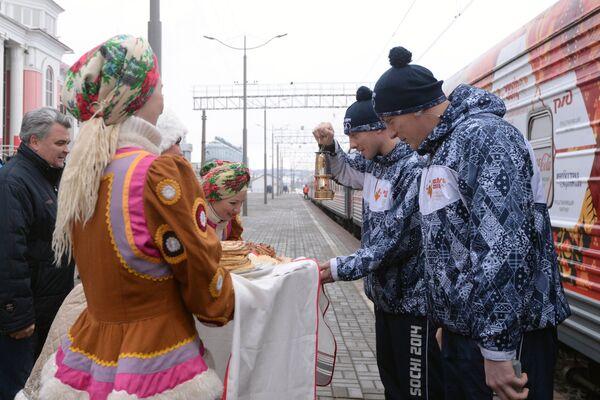 Мэр Саранска Петр Тултаев (слева на втором плане) встречает хранителей олимпийского огня на железнодорожном вокзале в Саранске