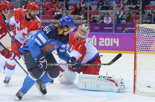 Форвард сборной Финляндии Микаэль Гранлунд забрасывает шайбу в ворота Семена Варламова (слева направо)