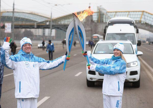 Российская фигуристка Екатерина Боброва и факелоносец Аким Афанасьев во время эстафеты паралимпийского огня в Москве