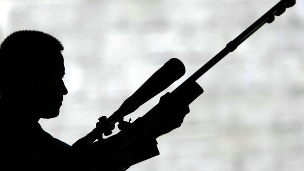 Силуэт стрелка с малокалиберной винтовкой по движущимся мишеням