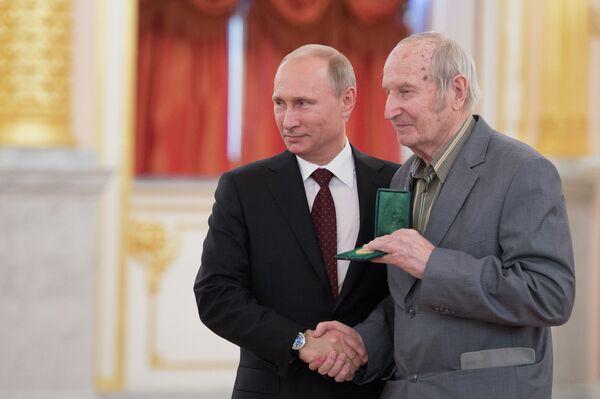 Президент России Владимир Путин (слева) вручает советскому хоккеисту Виктору Шувалову его золотую медаль с Олимпиады 1956 года