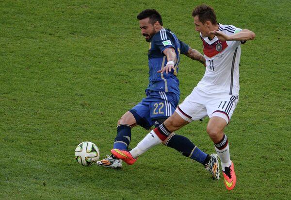 Форвард сборной Аргентины Эсекьель Лавесси (справа) и нападающий сборной Германии Мирослав Клозе