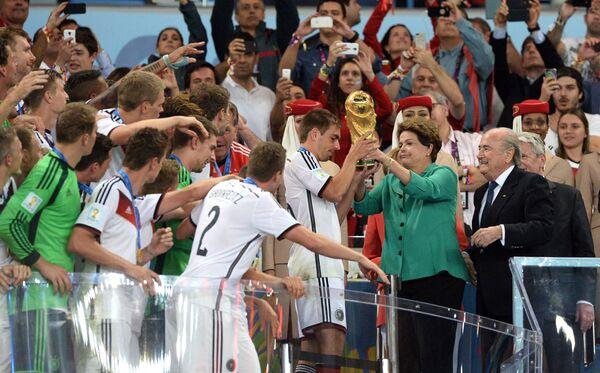 Президент Бразилии Дилма Руссефф вручает кубок турнира команде Германии