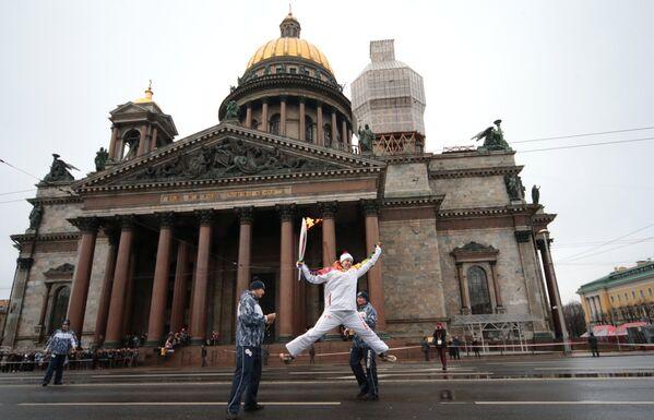 Факелоносец во время эстафеты олимпийского огня около Исаакиевского собора в Санкт-Петербурге