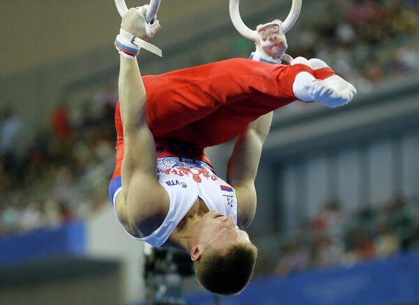 Денис Аблязин выступает в упражнении на кольцах на чемпионате мира по спортивной гимнастике