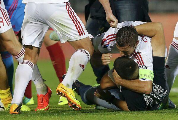 Полузащитник сборной Албании Лорик Цана дерется с сербским фанатом